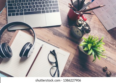 Desktop calendar glasses laptop eadphone clock diary and book on wooden desk.Diary for planning work schedules and appointments,Working space at home.Urban Lifestyle concept.
