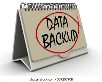 "Desktop calendar with inscription ""DATA BACKUP"" on the white surface"