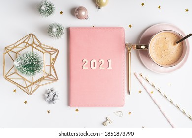 Desktop Christmas notepad with 2021 letters text. Flat lay of white table background with planner, cup of coffee, Christmas decoration and stationery.