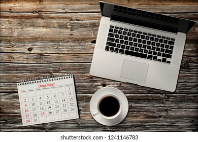 Desktop with computer, coffee and calendar for December 25
