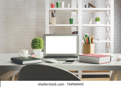 Desktop with empty white laptop screen, smartphone, supplies and other items. Creative designer office, education, occupation, freelance and lifestyle concept. Mock up