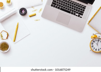 Desktop flatlay scene, laptop, notepad, pens along with other gold stationery items, on a plain white desk background. Negative space below.