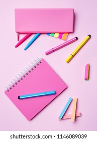 Desktop for girls. Notebook, pencil case, markers, pens, chalk and elastic on a pink background. Place for text