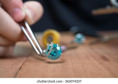 Desktop jeweler. jeweler holding tweezers silver ring with blue stone