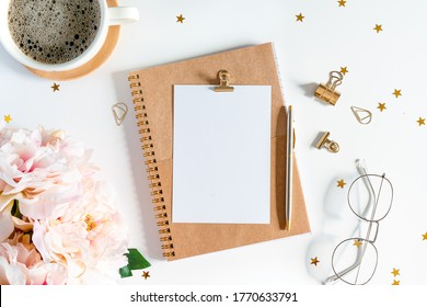 Desktop mock up planner. Flat lay of white working table background with cup of coffee putting on it. Top view glasses, flower, golden paper binder clips, blank greeting card, craft Notebook and pen.
