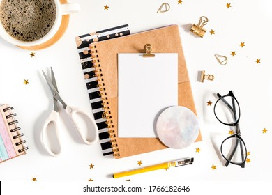 Desktop mock up, handmade DIY tools. Top view of white working table background with cup of coffee. Flat lay scissors, tapes, glasses, golden paper binder clips, blank greeting card, Notebook and pen.