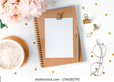 Desktop mockup planner . Flat lay of white working table background with cup coffee, stationery. Top view glasses, flower, golden paper binder clips, blank greeting card, craft Notebook and pen.