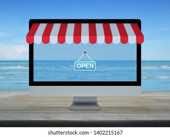 Desktop modern computer monitor with online shopping store graphic and open sign on wooden table over tropical sea and blue sky with white clouds, Business internet shop online concept