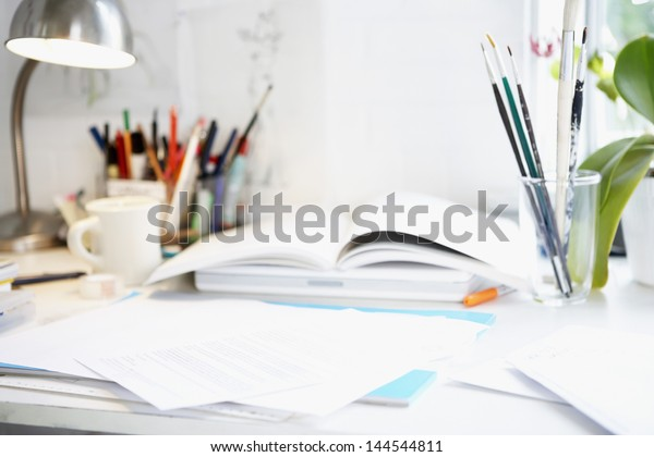 Desktop with papers, books, paint brushes, pens, and pencils