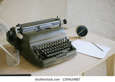 desktop, retro typewriter. Antique typewriter on a wooden table background with papers ready for a new book or a novel with many failing pages lined up on a desktop. office equipment. clock, pencil