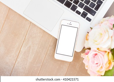 desktop scene with modern phone, laptop keyboard and flowers, copy space on blank sreen
