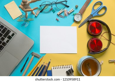 Desktop top view on colourful background table, modern style, workplace concept, with notebook, empty white page, and glasses, with copy space, Top view. Flat lay style.
