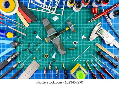 desktop view from above of assembly and painting of a  retro scale model plane concept background. modeling tools airbrush gun paint kit parts blue green cutting mat knife and brush on work desk.