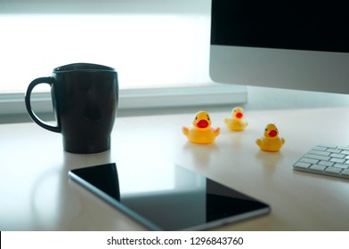 Desktop view with coffee cup tablet and rubber ducks