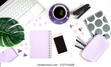Desktop workspace flat lay with hi-tech touch screen laptop and modern purple, black and white accessories on white background.
