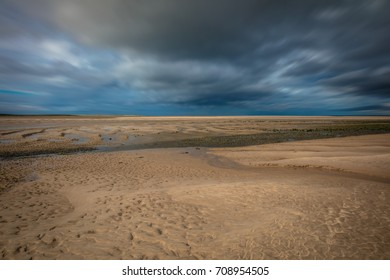 Desolate Beach with Sand, Sky and Clouds