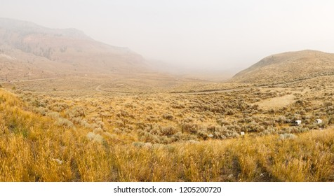 Desolate desert highway scene with forest fire smoke  in Kamloops, British Columbia, Canada