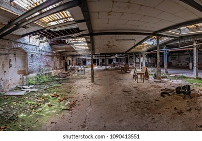 Desolate hall of a factory ruin. Light rays are shining through the broken windows