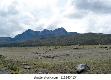 Desolate, high altitude landscape of scrub grass studded with rocks below the peak of Cotopaxi Volcano, Ecyador