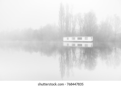 Desolate Houseboat in the fogg on the ringvaart in Amsterdam, the Netherlands.