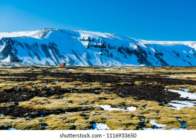 Desolate landscape with a lonely cabin on lichen covered volcanic field of rocks with massive snow covered mountains in the background, iceland april 2018