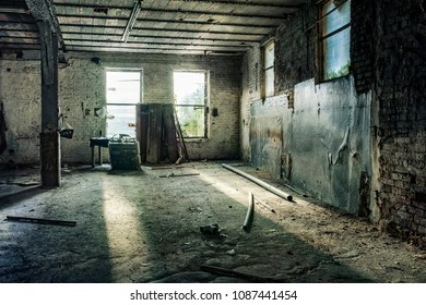 Desolate room of a factory ruin. Light rays are shining through the broken windows