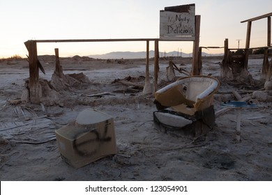 A desolate Salton Sea post-apocalyptic scene of a broken chair in front of a TV in a desert.
