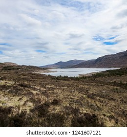 Desolate view of brown heathland with lake and mountains in background - Isle of Skye, Scotland