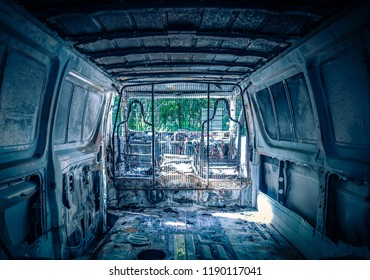 Desolated grey van from inside with dirty rusty parts with green foliage on background