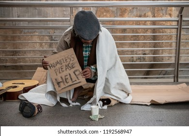 Despair homeless sitting on public walkway, holding helping sign and waiting for merciful people to give him money or food. Poor old man waiting for help with sad.