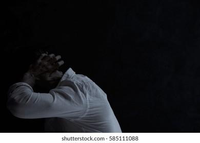 Despair man covering his ears, sitting in dark room