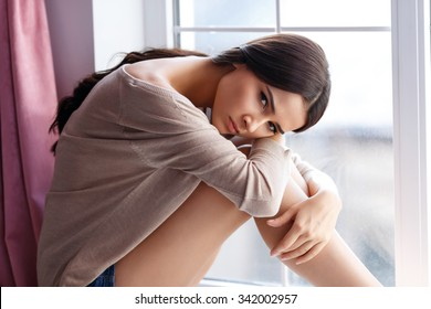 In despair. Pleasant attractive young moody girl sitting on the window sill and leaning on her legs while mulling over