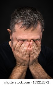 Despair. Portrait of an elderly man with face closed by hand