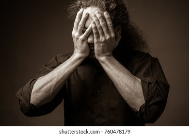 Despair. Portrait of a man with hands on his face. Sepia