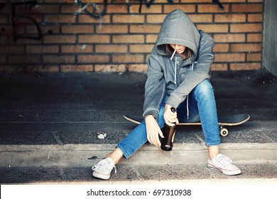 Despair Teenager Girl Sitting in the Dark Doorway and Smoking a Cigarette with Beer in a Sweatshirt with a Hood