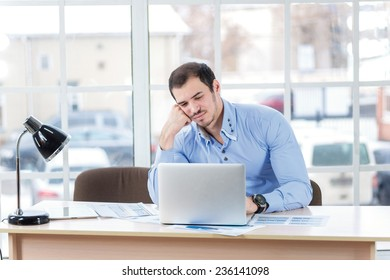 Despair at work. uncertain businessman resting his laptop and bent over a laptop while handsome young man sitting in the office at the table.