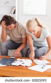 Despaired couple calculating their expenses in the living room