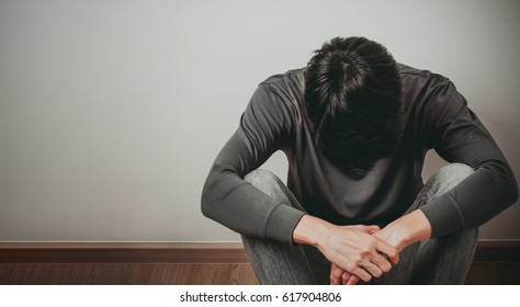 Despaired man hug his knee and cry when sitting alone on the floor at corner of the room