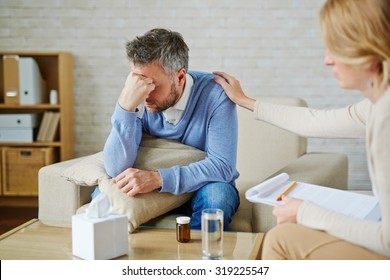 Despaired man with pillow and handkerchief being reassured by his psychologist