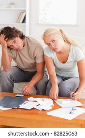 Despaired stressed couple calculating their expenses in the living room