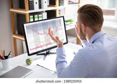 Despairing businessman faced with financial losses sitting at his desk consulting graphs on monitors
