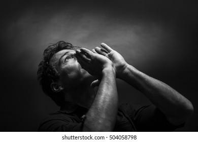 Despairing man screaming. Low key black and white portrait