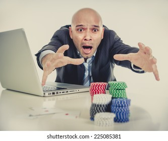 desperate addict businessman on computer laptop loosing lots of money betting on internet poker with cards and chips on online gambling addiction isolated on clear background