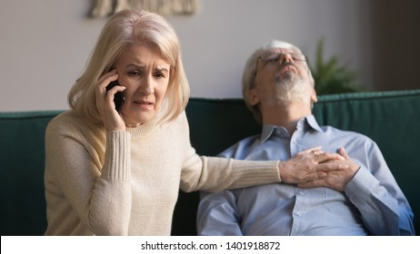 Desperate aged wife holds phone makes 911 emergency call while her sixty years husband lies on couch, man feeling crushing chest pain, loss of blood supply, shortness of breath, heart attack concept