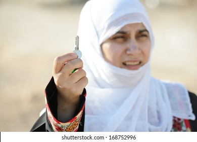 Desperate Arabic woman on Middle East holding key of lost home