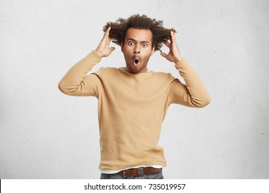 Desperate astonished male looks at camera with jaw ropped out, tears hair out, finds out horrified news on television, feels crazy and mad. Hipster man shocked with sale prices on clothes in shop