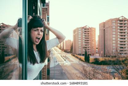 Verzweiflte Frau guckt während der Quarantäne über die Covid-19-Krise aus dem Fenster. Bleiben Sie bei Ihrem Konzept. Leere Stadt unter Einschluss. Häuslicher Missbrauch und Gewalt. Valladolid, Spanien.
