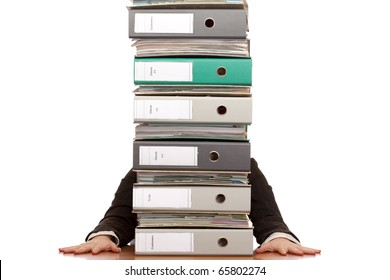 Desperate business woman sits behind folder stack. Isolated on white background.