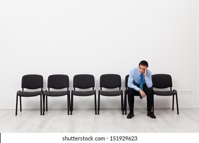 Desperate businessman or employee sitting alone propping his head