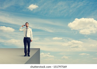 desperate businessman with gun standing on the edge